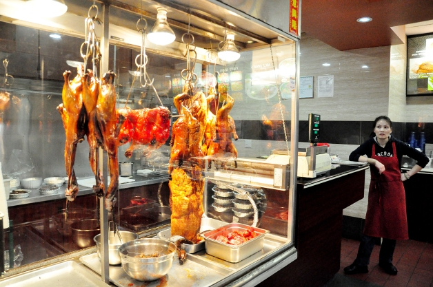 Caramelized BBQ duck and chicken hang on display in the warmer at the counter, where staff will pull orders and customize each.